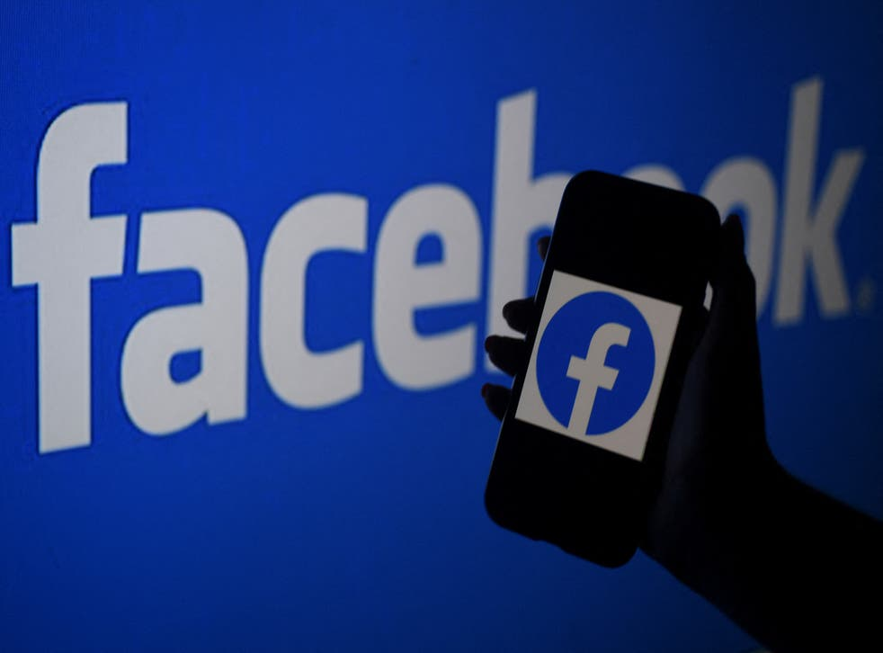 A smart phone screen displays the logo of Facebook on a Facebook website background