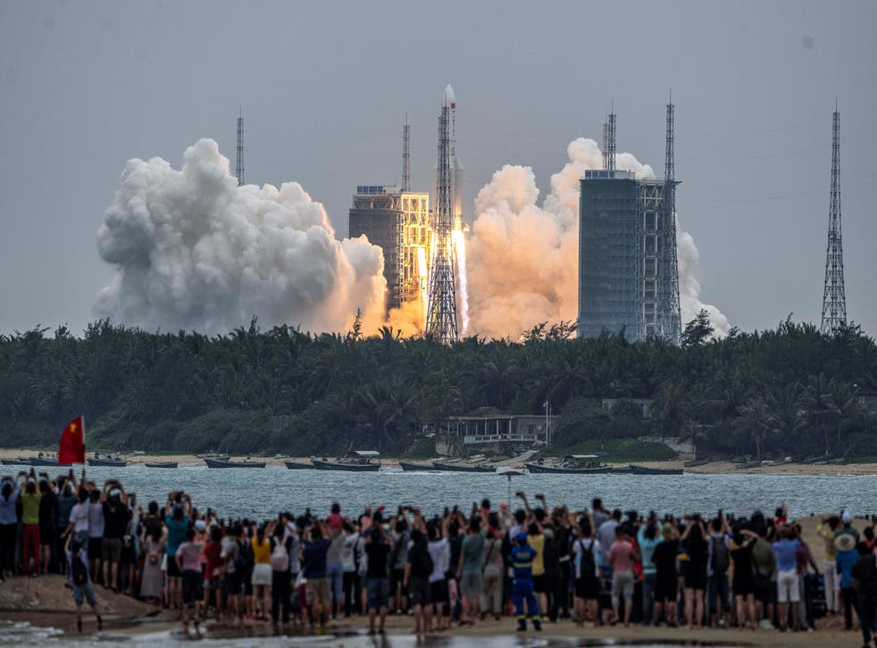 People watch a Long March 5B rocket, carrying China's Tianhe space station core module, as it lifts off from the Wenchang Space Launch Center in southern China's Hainan province
