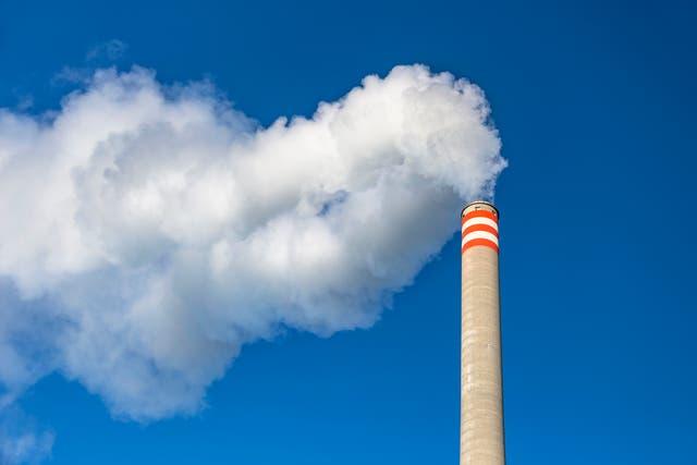 Los gases que se descargan de la chimenea industrial hacia el cielo