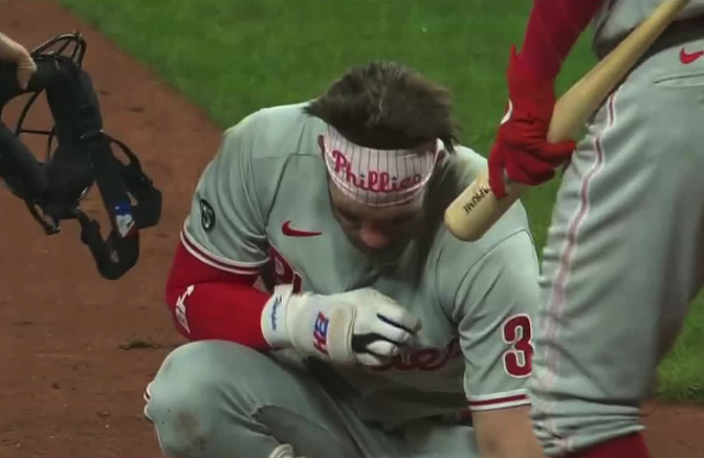 Bryce Harper recovers after being hit in the face with a fastball pitch