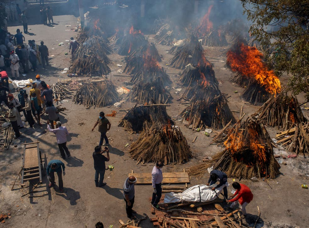 <p>File: In this 24 April photo, multiple funeral pyres of victims of Covid-19 burn at a ground that has been converted into a crematorium in Delhi</p>