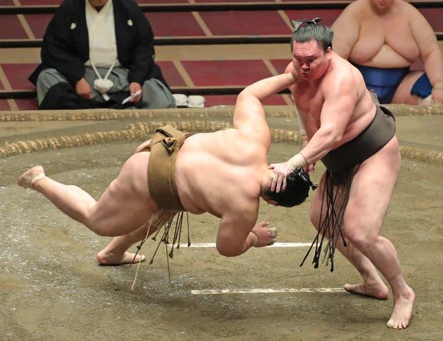 <p>Yokozuna-ranked sumo wrestler Hakuho (R) pushes down opponent Kagayaki in the ring in 2020</p>