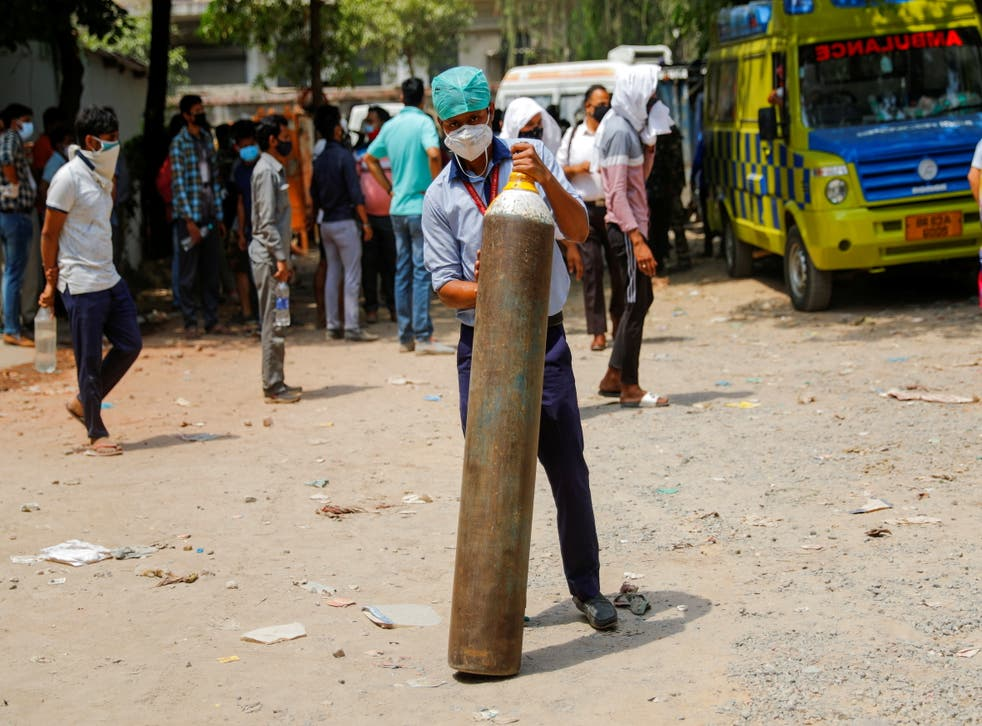 <p>File: A healthcare worker holds an oxygen cylinder outside a factory as he waits to get it refilled</p>