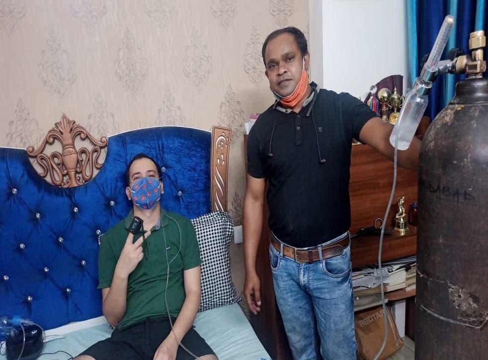 <p>Devendra Kumar Rai (black t-shirt) brought an oxygen cylinder from over 1,400 kilometres away for his childhood friend Rajan Kumar Singh (green t-shirt) who is suffering from coronavirus infection      </p>