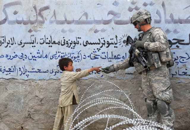 <p>US soldier  presents a gift to an Afghan child during a patrol at Khogiani in Langarhar in 2010</p>