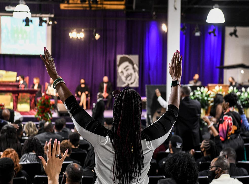 <p>A woman raises her hands as she prays during the funeral of Daunte Wright </p>