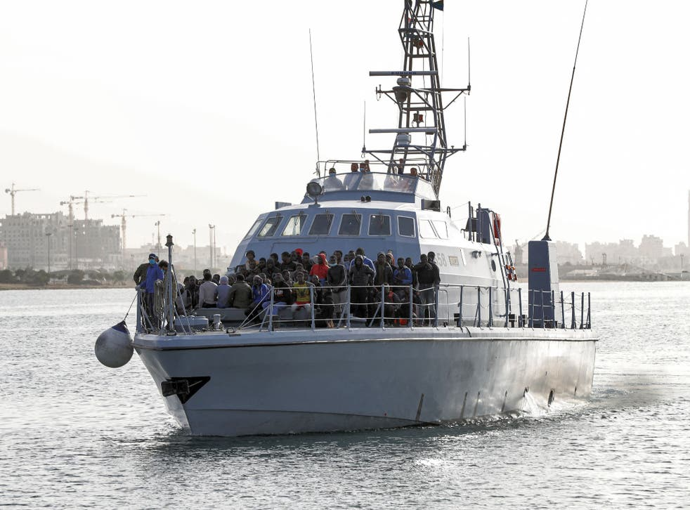 <p>Refugees and migrants arrive at the naval base in the Libyan capital of Tripoli having been picked up at sea</p>