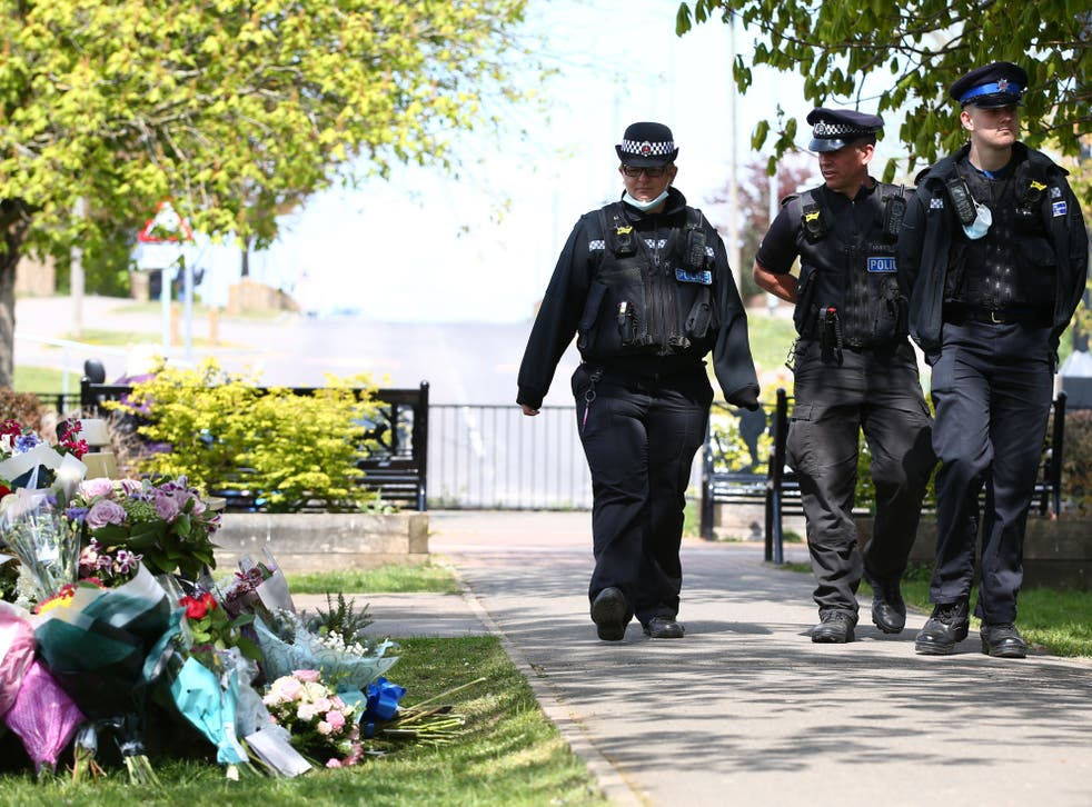 <p>Police officers view floral tributes for murdered PCSO Julia James in Aylesham</p>