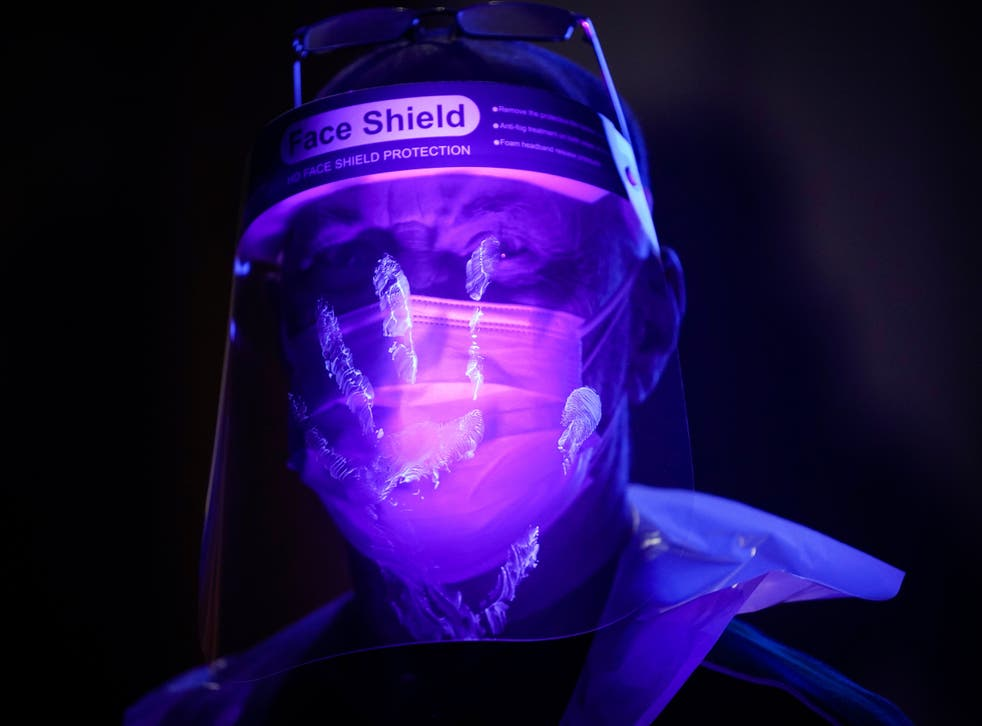 <p>St John Ambulance instructor Keith Vickers is illuminated by ultra violet light to demonstrate how bacteria and contamination can be spread as he trains volunteers</p>