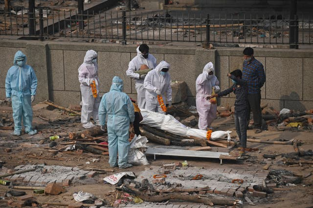 <p>Relatives and friends wearing personal protective equipment (PPE) suits prepare the body of a victim who died due to the Covid-19</p>