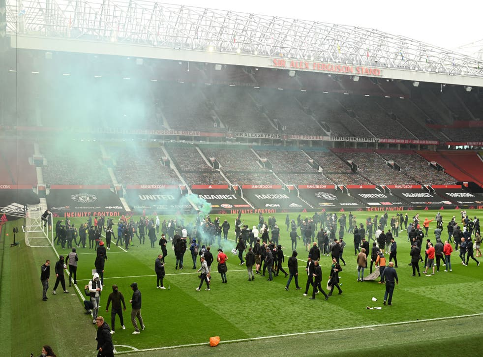 <p>Manchester United fans storm the pitch at Old Trafford</p>