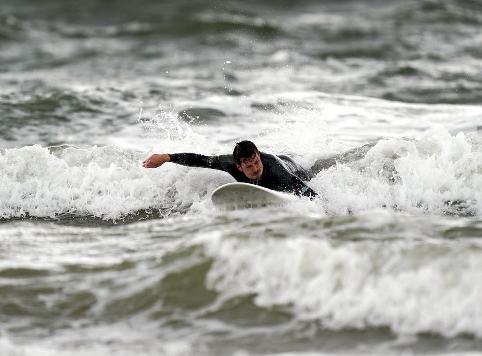 A surfer enjoys the waves in Porthcawl, Wales