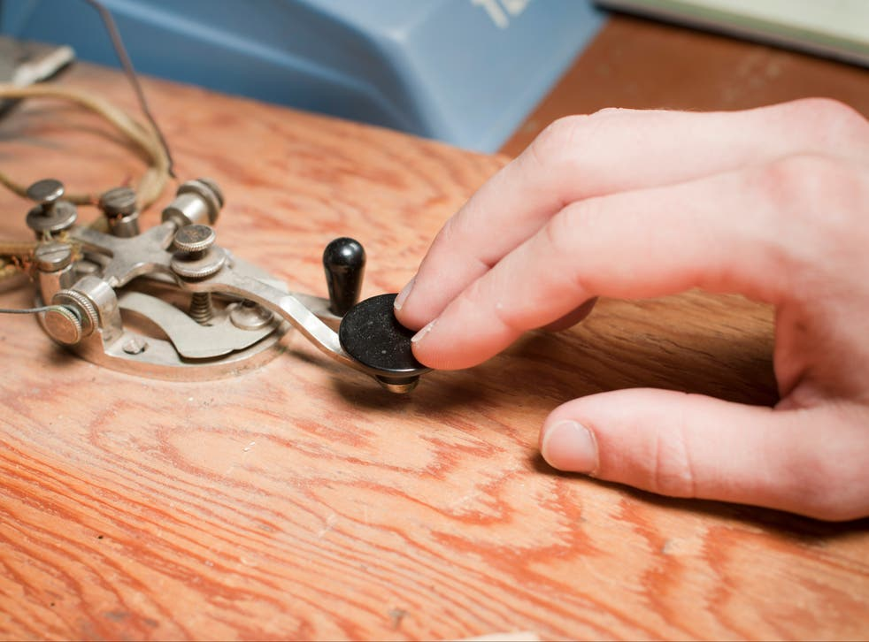 A man works a telegraph key at a desk.