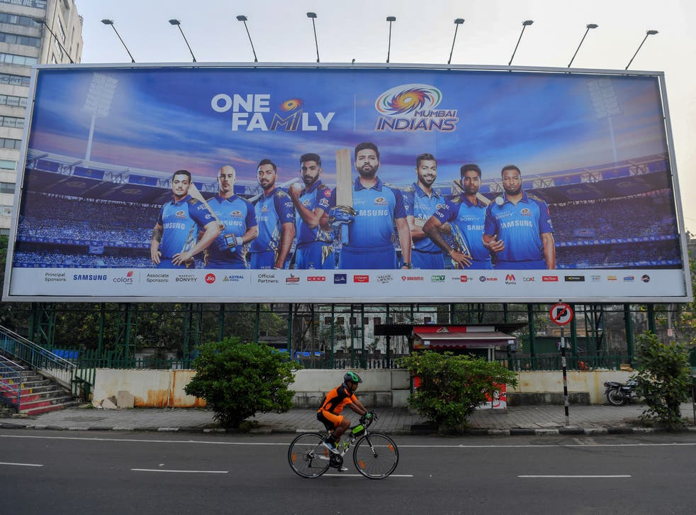 A cyclist rides past a hoarding of Mumbai Indians cricketers of the Indian Premier League