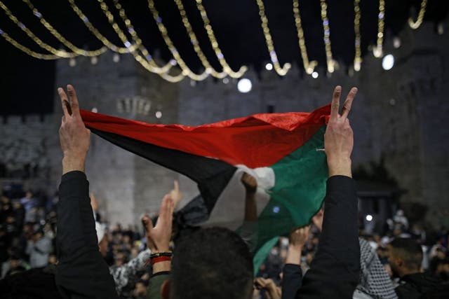 <p>Palestinian protesters wave the national flag outside the Damascus Gate in Jerusalem's Old City on 26 April, 2021</p>