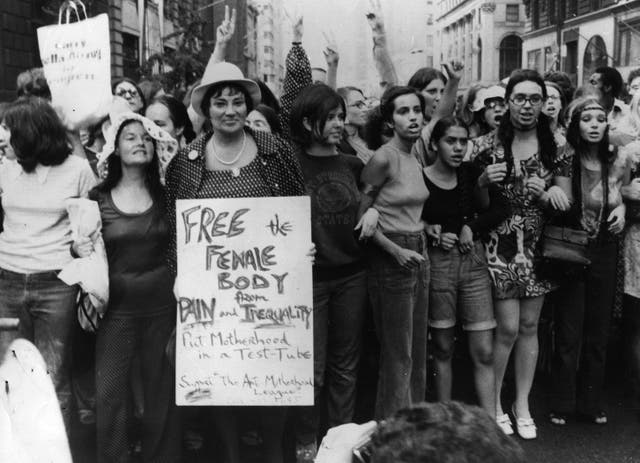 <p>Bella Abzug carries an anti-motherhood sign on the 50th anniversary of women winning the vote in the United States</p>