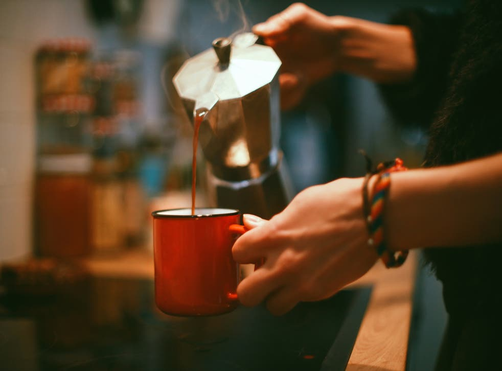 A woman's hands while she's pouring coffee into a cup