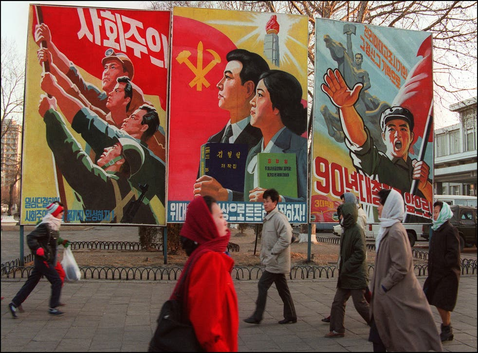 <p>Pedestrians walk past giant propaganda boards in central Pyongyang, 1995</p>