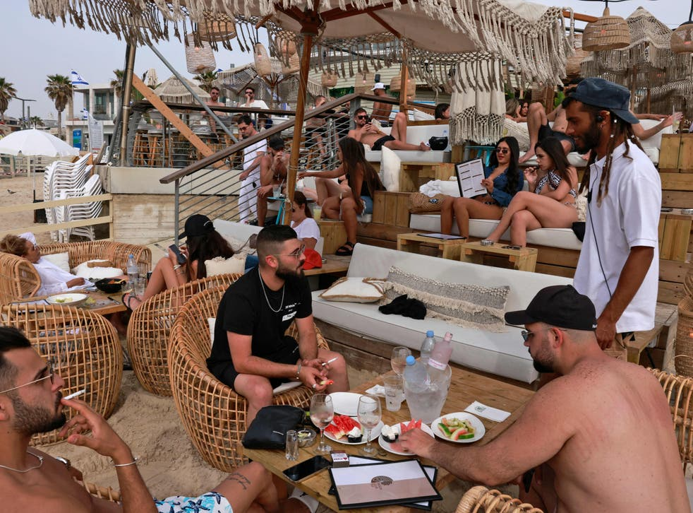 People relax at a beach bar in the Israeli coastal city of Tel Aviv on 19 April after authorities announced face masks were no longer needed outside