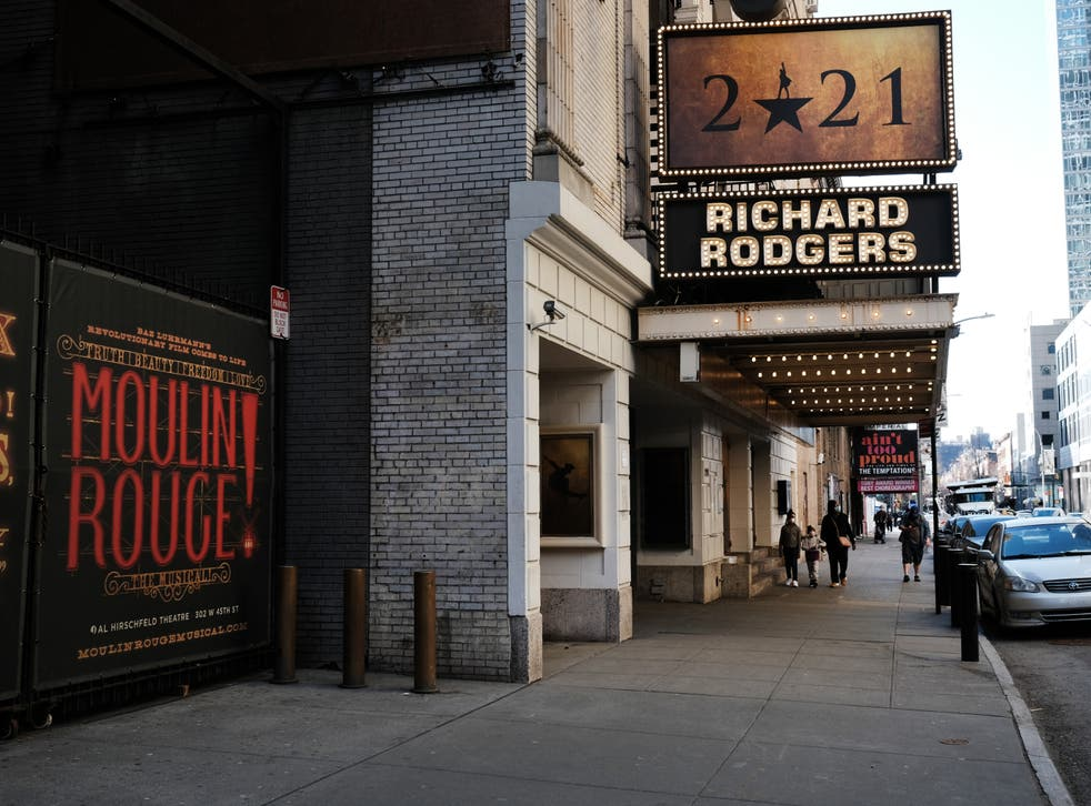 People walk through the empty Broadway theater district one year after it was closed due to Covid-19 restrictions on 12 March 2021 in New York City