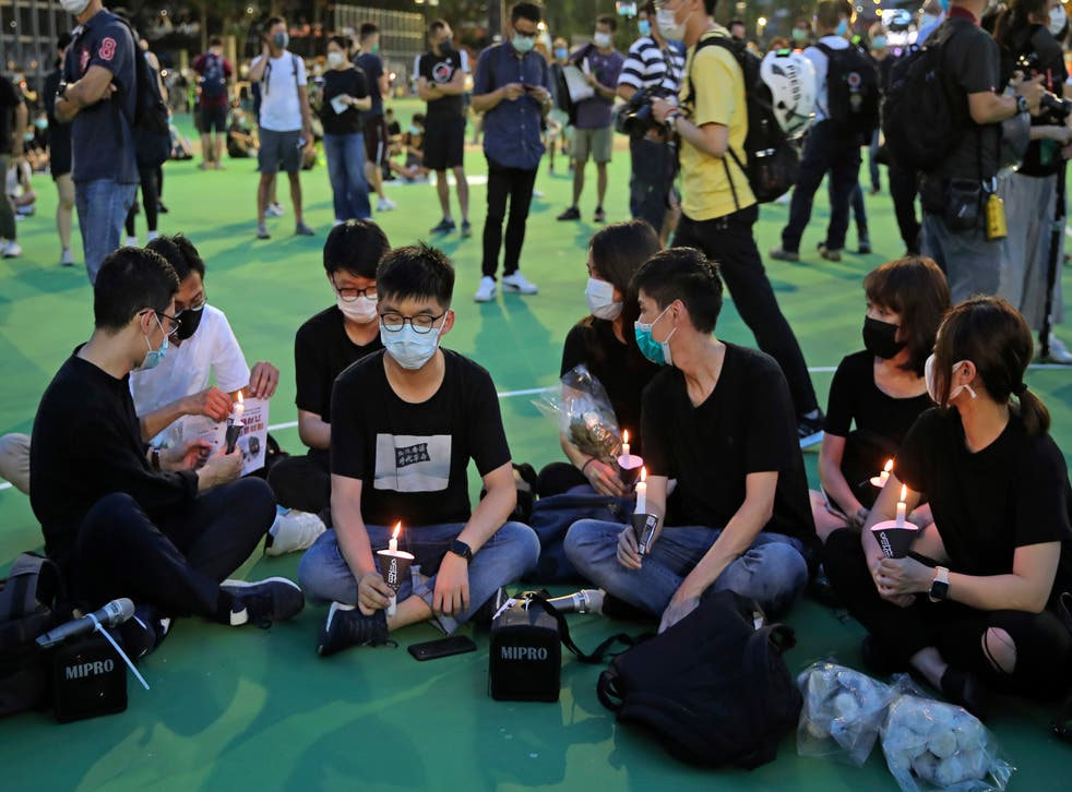 <p>Hong Kong democracy activist Joshua Wong, second left, at the 4 June 2020 vigil for the victims of the 1989 Tiananmen Square Massacre </p>