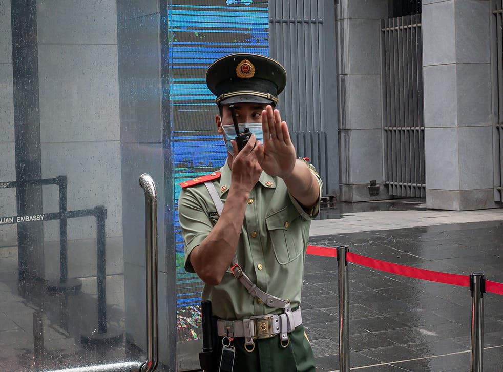 """<p>FILE. A Chinese paramilitary police officer gestures and speaks over his two-way radio while standing at the entrance gate of the Australian embassy in Beijing on July 9, 2020. - China has suspended """"indefinitely"""" its key economic dialogue with Australia.</p>"""