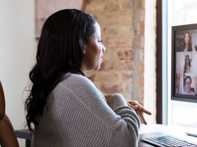 A woman uses video conferencing to chat with colleagues