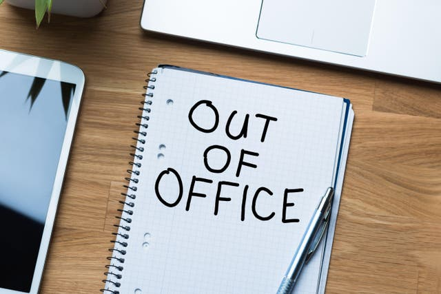 'Out of office' written on notepad on desk