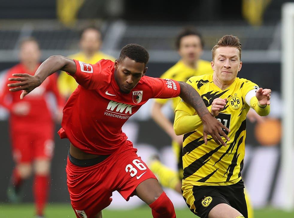 Reece Oxford vies for the ball against Borussia Dortmund's Marco Reus