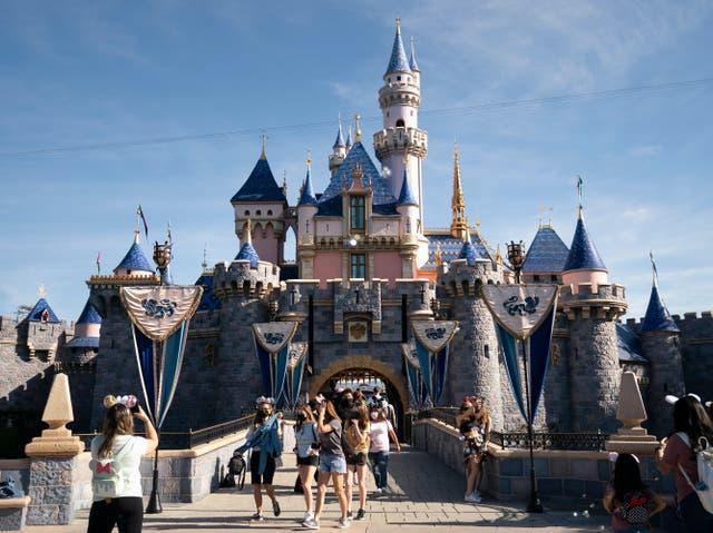 Los visitantes salen del Castillo de la Bella Durmiente en Disneyland en Anaheim, California, el 30 de abril de 2021