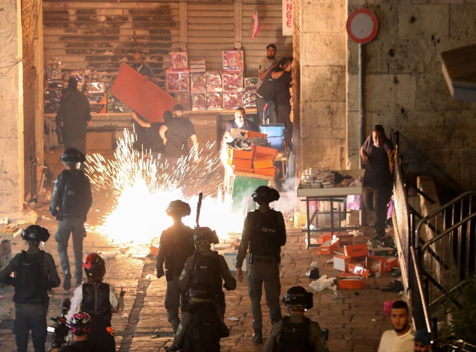 <p>Palestinians react as Israeli police fire a stun grenade during clashes at Damascus Gate</p>