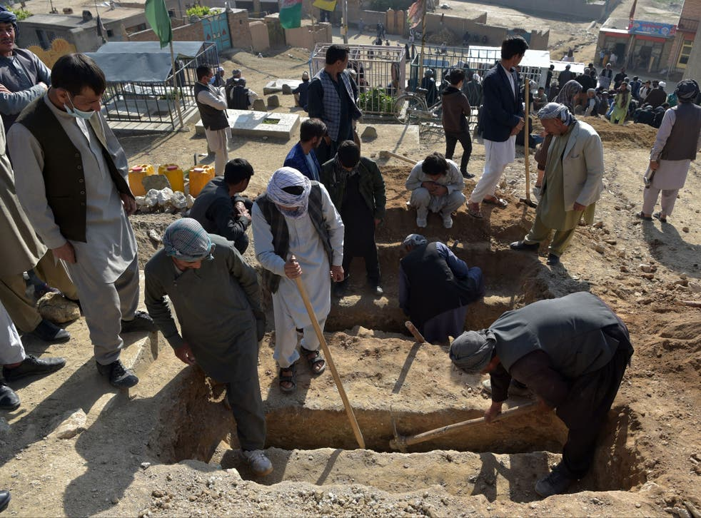 Shiite mourners and relatives dig graves for schoolgirls who died in multiple blasts outside a school in Kabul