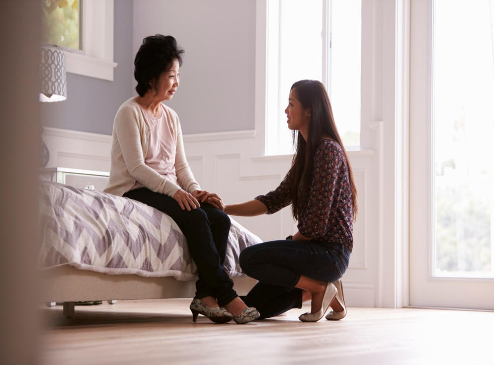 adult daughter talking to mother in bedroom