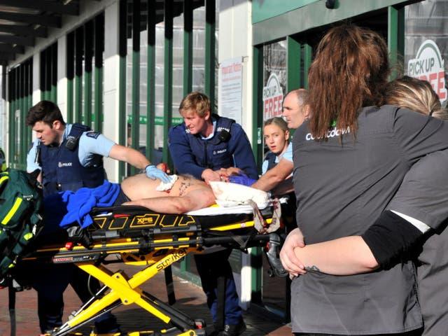 Una víctima del apuñalamiento del supermercado es llevada al hospital mientras el personal de la tienda se abraza afuera