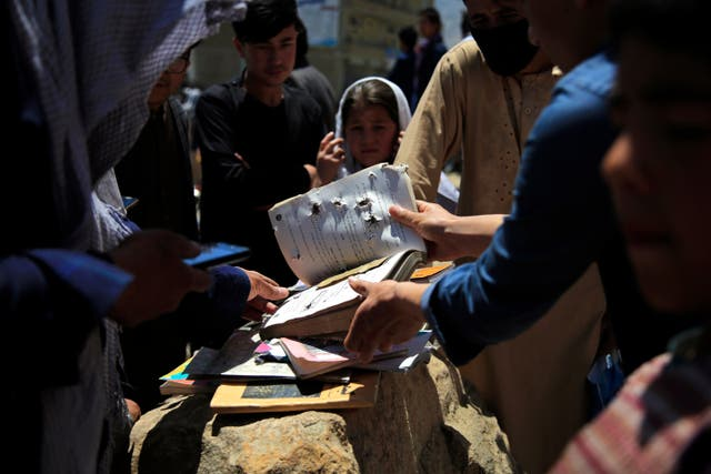 <p>Afghans go through belongings left behind after deadly bombings on Saturday near a school in Kabul, Afghanistan, Sunday, on 9 May, 2021</p>