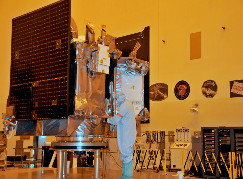 The OSIRIS-REx spacecraft sits on its workstand August 20, 2016 while an engineer checks the protective covering in a servicing building at Kennedy Space Center, Florida