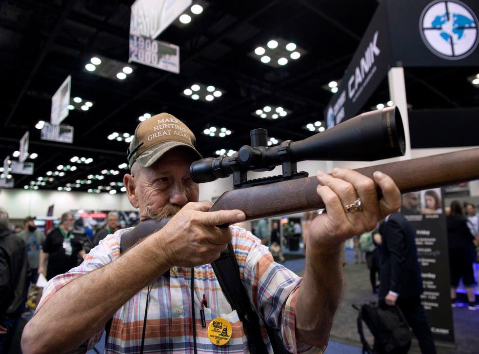 <p>Mark McKenzie of Tulsa, Oklahoma, looks through the scope of a deactivated rifle at the 2019 National Rifle Association (NRA) Annual Meetings and Exhibits in Indianapolis, Indiana, on April 26, 2019. </p>