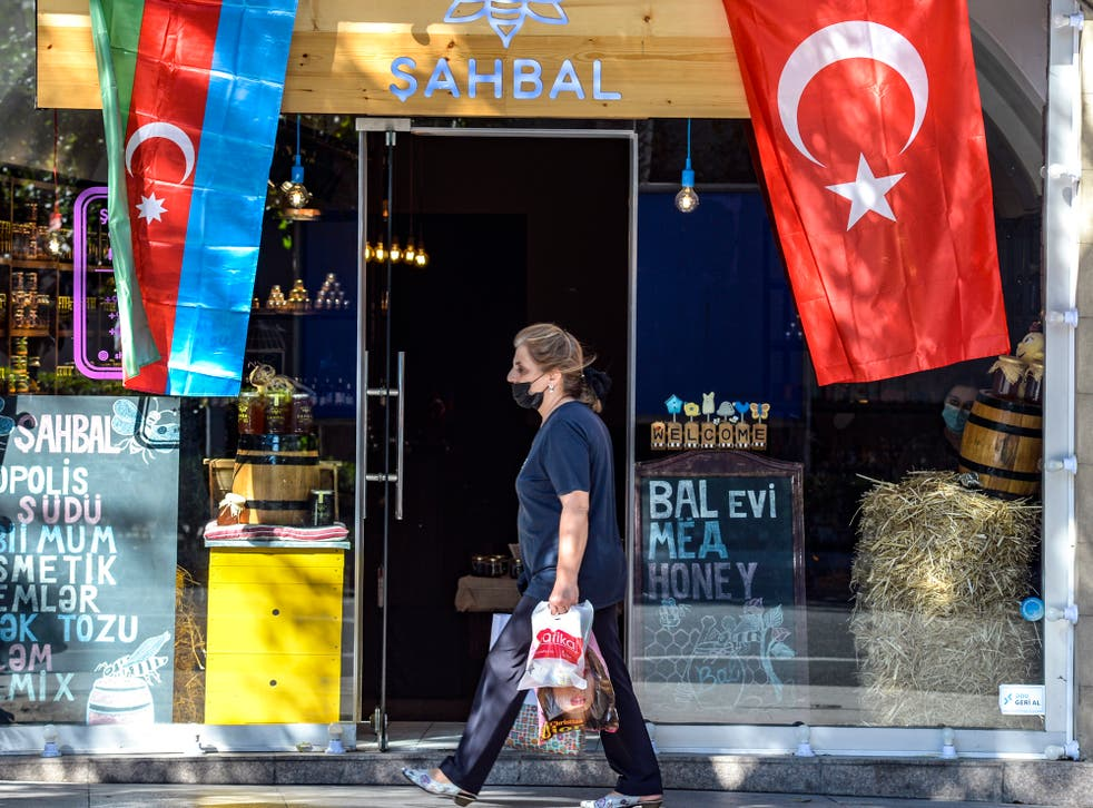 <p>Woman strolls past shop in Azerbaijani capital of Baku </p>