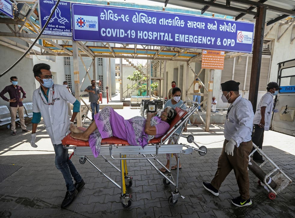 Indian health workers bring a suspected Covid-19 positive patient into a hospital in Ahmedabad, India