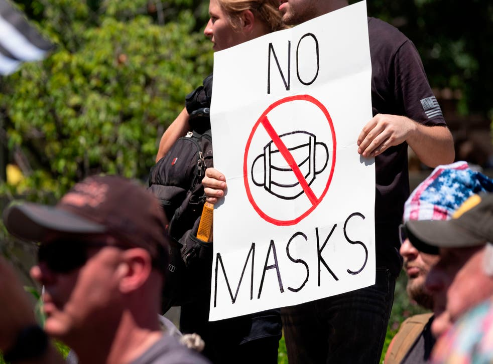 """An anti-mask protestor holds up a sign in front of the Ohio Statehouse during a right-wing protest """"Stand For America Against Terrorists and Tyrants"""""""