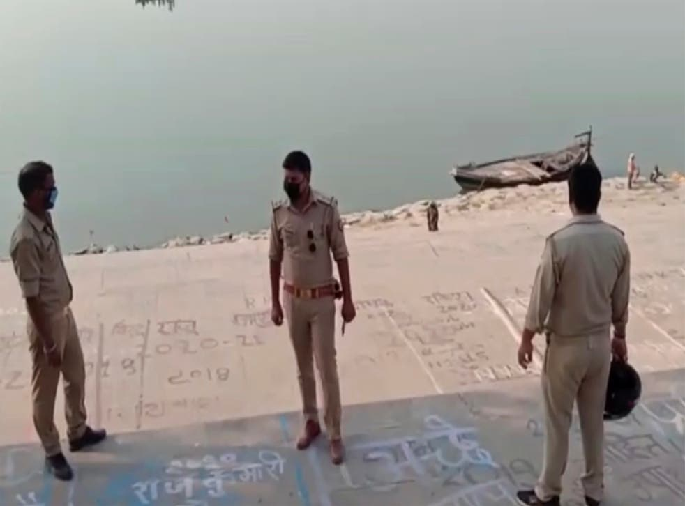 <p>Frame grab from video provided by KK Productions shows police officials stand at the banks of the river where several bodies were found in Ghazipur district in Uttar Pradesh on 11 May, 2021.</p>
