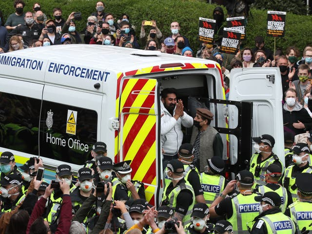 One of the men thanks crowds as he is freed from the immigration van