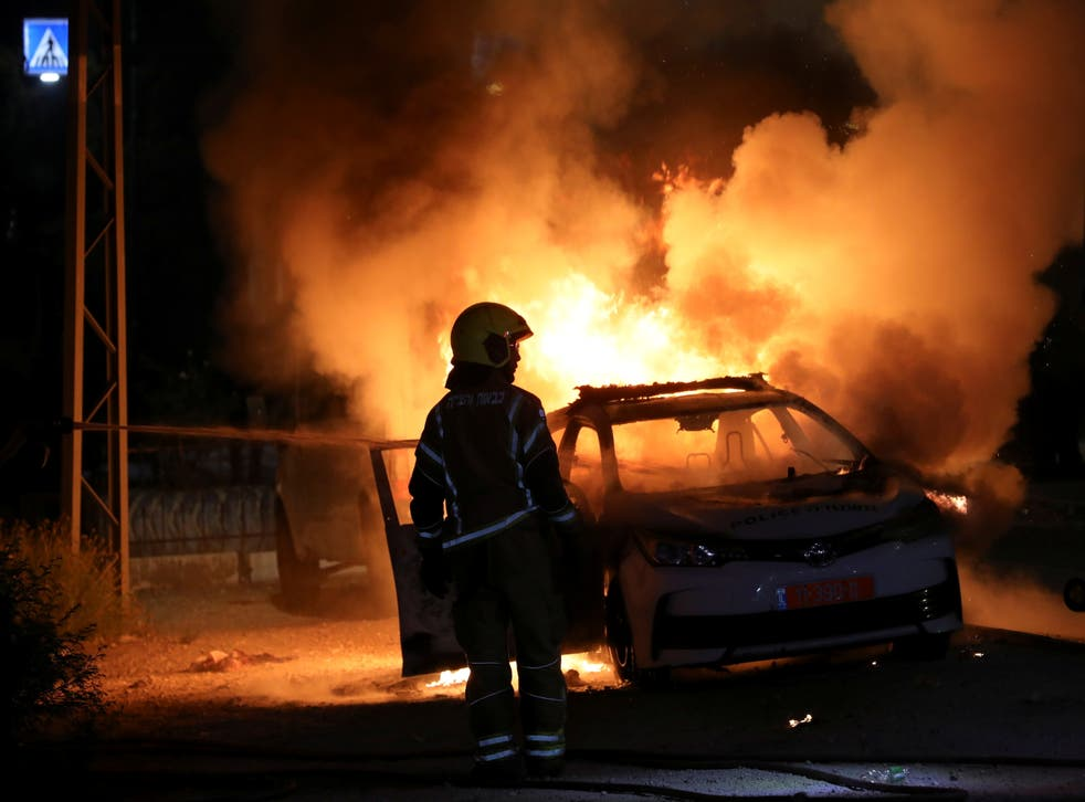 <p>An Israeli firefighter by a burning police car in Lod</p>