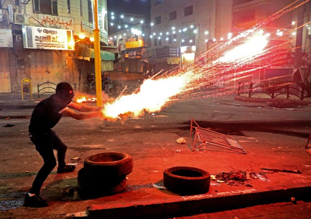 A Palestinian protester launches flares amid clashes with Israeli soldiers in the city centre of Hebron in the West Bank