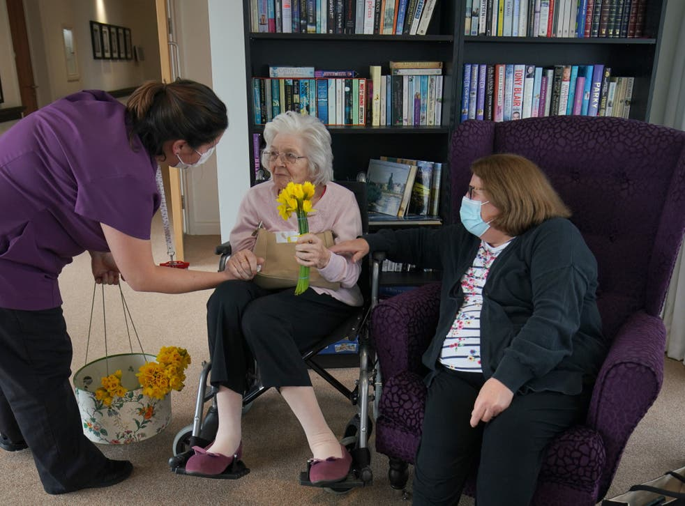 A member of staff gives a bunch of daffodils to Sylvia Newsom (centre) and her daughter Kay Fossett (right), who haven't seen each other since December, enjoy their first visit following the easing of rules at Gracewell of Sutton care home in South London
