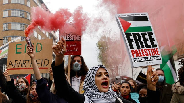 Pro-Palestinian activists and supporters let off smoke flares, wave flags and carry placards during a demonstration in support of the Palestinian cause as violence escalates in the ongoing conflict with Israel, in central London