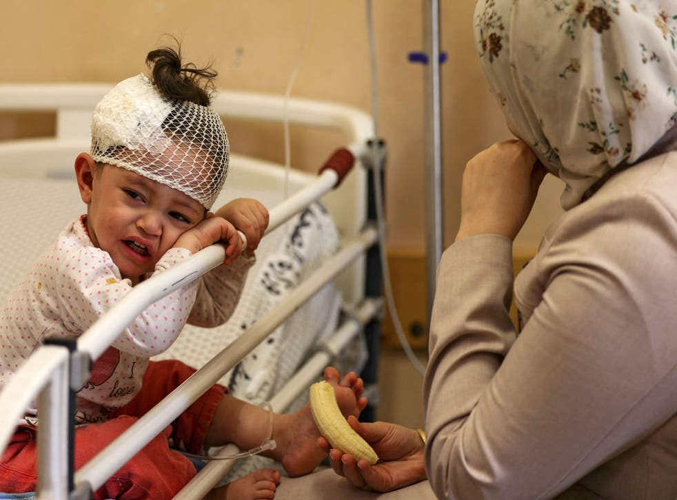 <p>A Palestinian mother sits with her daughter, who was wounded in overnight Israeli air strikes on the Gaza Strip</p>