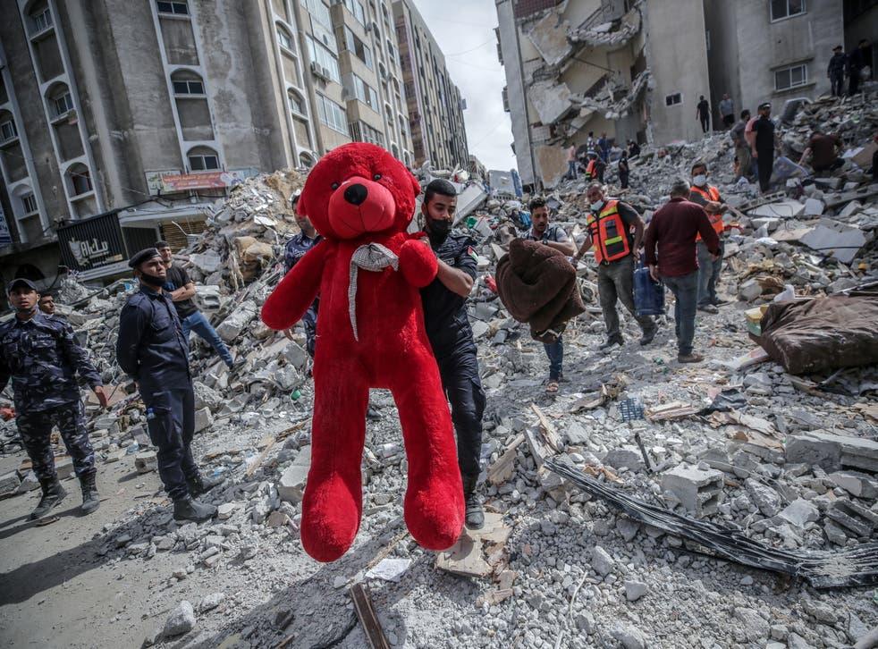 Un palestino sostiene un oso de peluche entre los escombros de las casas destruidas después de un ataque aéreo israelí en la ciudad de Gaza.