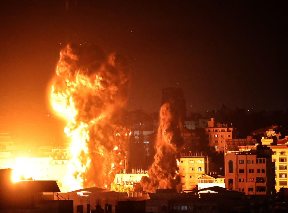 Fire and smoke rise above buildings in Gaza City as Israeli warplanes target the Palestinian enclave, early on 17 May, 2021.