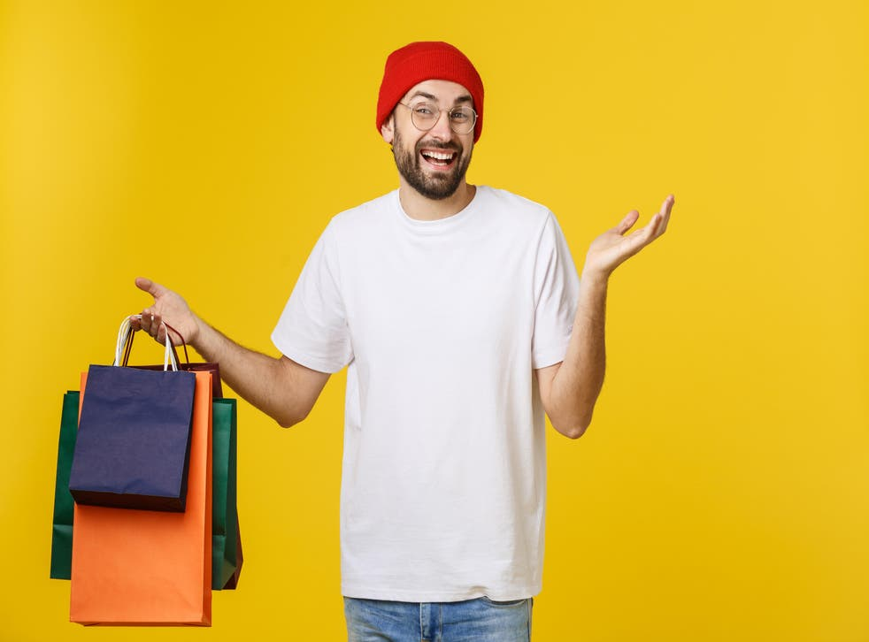 Bearded man with shopping bags with happy feeling isolated on yellow bacground